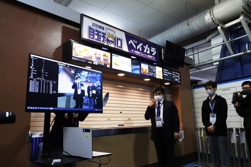 横浜スタジアムにおける技術実証(プレゼン時の様子)。要所にカメラを設置し、人流や着席・離席、マスクの有無・着脱を把握(NECが協力)。「認識」技術までの採用とし、「認証」による個人の特定はしていない(写真:安川 千秋)