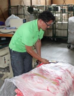 ふじみ野産業での作業の様子。花嫁わたからの商品のバーコードを読み込んで、ふとんを打ち直す。中の綿を足すことも多いという。